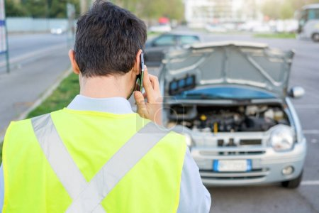 Photo for Upset man calling assistance mechanic service after car breakdown - Royalty Free Image