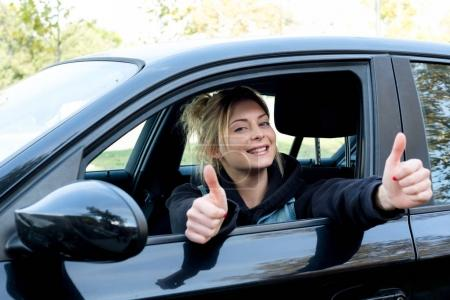 Happy girl with thumb up driving her new car