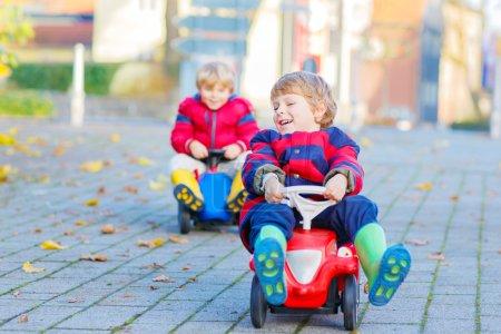 Foto de Dos chicos poco colorida ropa y botas de lluvia conduce coches de juguete. Gemelos haciendo competencia al aire libre. Ocio activo para niños en día de otoño - Imagen libre de derechos