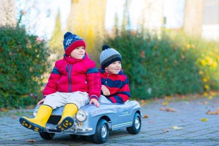 Foto de Dos chicos poco en ropa colorida y botas de lluvia conduce coche viejo y haciendo competencia al aire libre. Ocio activo para niños en día de otoño - Imagen libre de derechos