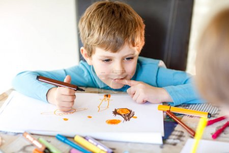 Photo for Cute little preschool kid boy at school making homework, painting a story with colorful pens. Little child writing with pencils, indoors. Elementary school and education, imagine fantasy concept. - Royalty Free Image