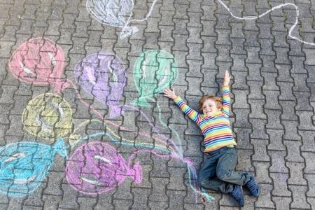 Photo pour Adorable petit garçon qui s'amuse avec des ballons colorés dessin d'image avec des craies sur le sol. Loisirs créatifs pour les enfants à l'extérieur en été, célébration d'anniversaire, idée d'invitation de carte - image libre de droit