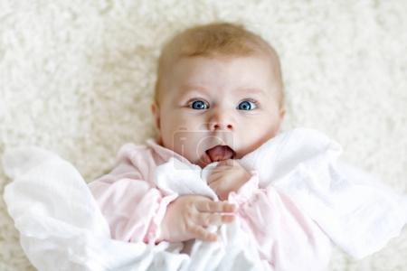 Photo pour Gros plan d'une petite fille de deux ou trois mois aux yeux bleus. Enfant nouveau-né, petite adorable fille paisible et attentive regardant surpris par la caméra. Famille, nouvelle vie, concept d'enfance - image libre de droit