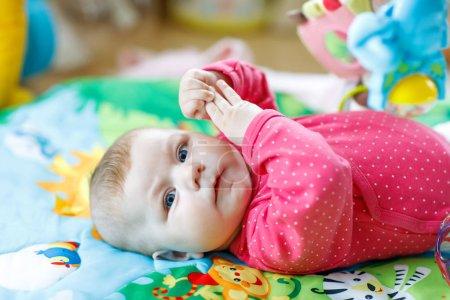 Photo pour Bébé adorable mignon nouveau-né jouant sur la salle de gym jouet coloré et regardant la caméra. Gros plan d'enfant paisible, petite fille apprenant à saisir. Famille, naissance, nouvelle vie. Enfant attentif . - image libre de droit