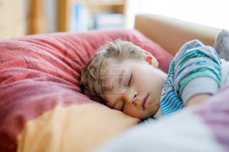 Photo for Little sad preschool kid boy sleeping. Tired schoolchild resting after school classes. Blond boy on colorful bed. - Royalty Free Image