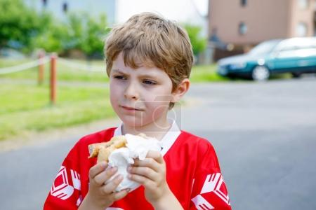 Little blond kid boy eating hot dog after playing soccer.