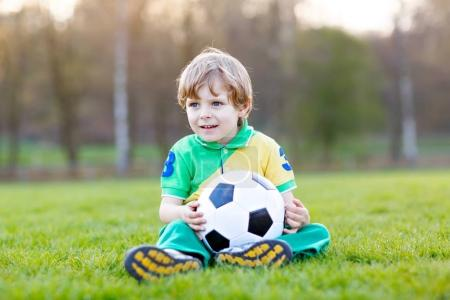 Photo for Little cute kid boy of 4 playing soccer with football on field, outdoors. Active child making sports with kids or father, Smiling happy preschool boy having fun in summer. - Royalty Free Image