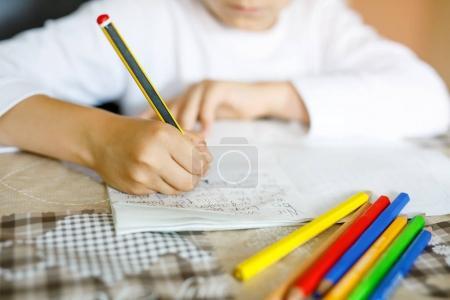 Photo pour Enfant faisant ses devoirs et écrivant un essai d'histoire. Classe primaire ou primaire. Gros plan des mains et crayons colorés . - image libre de droit