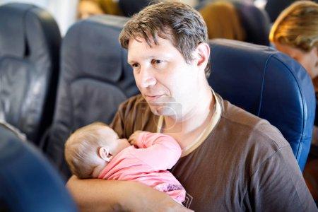 Photo pour Jeune père fatigué et sa petite fille endormie pendant le vol en avion en vacances. Papa tenant la petite fille sur le bras. Voyage en avion avec bébé, enfant et concept familial . - image libre de droit