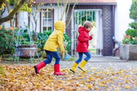 Photo pour Deux petits meilleurs amis et enfants garçons parc d'automne en vêtements colorés. Joyeux frères et sœurs enfants qui s'amusent en imperméables rouges et jaunes et bottes en caoutchouc. Famille jouant à l'extérieur. loisirs actifs - image libre de droit