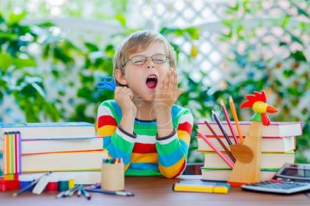 Photo for Funny little kid boy with glasses and lots of pupils stuff like crayons pens, scissors and books. Tired child and student is back to school and happy about begin of lessons. - Royalty Free Image