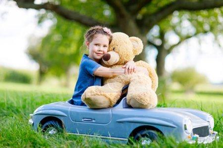 Photo pour Fille de petit enfant d'âge préscolaire grosse voiture de jouet ancien vintage de conduite et de s'amuser avec la lecture avec ours peluche grande, à l'extérieur. Enfant bénéficiant chaude journée d'été dans le paysage naturel. Voiture conduite fille. - image libre de droit