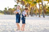 Two little kids boys having fun on tropical beach