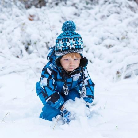 Photo pour Portrait d'hiver d'un enfant garçon en vêtements colorés, à l'extérieur pendant les chutes de neige. Extérieurs actifs loisirs avec les enfants en hiver par temps froid et neigeux. Bébé heureux enfant s'amuser avec de la neige dans la forêt - image libre de droit
