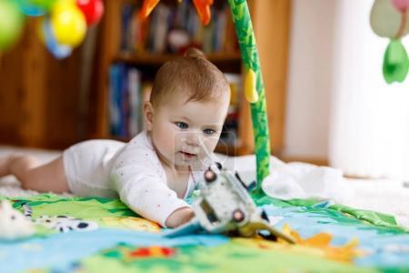 Photo pour Adorable petite fille de jouer avec des jouets éducatifs en pépinière. Enfant sain heureux s'amuser avec des jouets colorés différents à la maison. Bébé mignon apprentissage saisir et tenir des choses et des jouets, assis et de ramper - image libre de droit