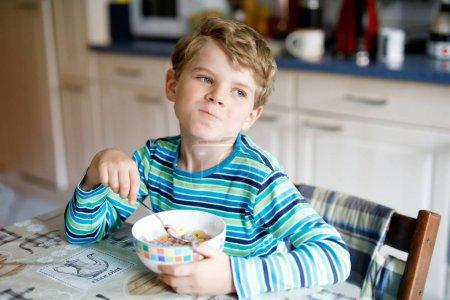 Photo pour Adorable petit écolier blond qui mange des céréales avec du lait et des baies pour le petit déjeuner ou le déjeuner. Une alimentation saine pour les enfants, les écoliers. À la cantine scolaire ou à la maison . - image libre de droit