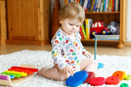 Photo for Adorable cute beautiful little baby girl playing with educational wooden toys at home or nursery. Toddler with colorful stack pyramid and music toy. Happy healthy child having fun with different toys. - Royalty Free Image