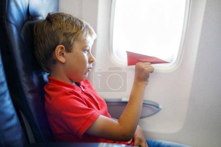Photo pour Petit garçon jouant avec l'avion en papier rouge pendant le vol en avion. Enfant assis à l'intérieur d'un avion près d'une fenêtre. Famille en vacances . - image libre de droit
