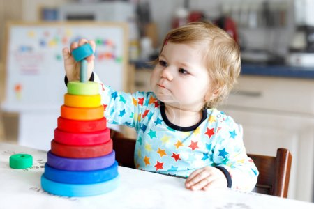 Photo for Adorable cute beautiful little baby girl playing with educational toys at home or nursery. Happy healthy child having fun with colorful wooden rainboy toy pyramid. Kid learning different skills - Royalty Free Image