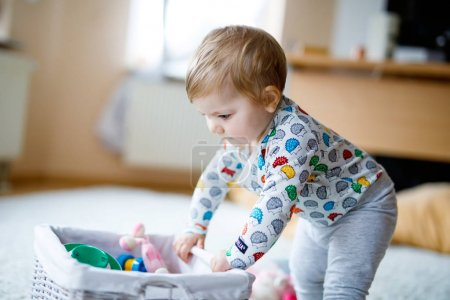Photo for Adorable cute beautiful little baby girl playing with educational toys at home or nursery. Happy healthy child having fun with colorful different toys. Kid learning different skills - Royalty Free Image