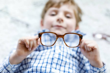 Photo for Close-up portrait of little blond kid boy with different eyeglasses on white background. Happy smiling child in casual clothes. Childhood, vision, eyewear, optician store. Boy choosing new glasses - Royalty Free Image