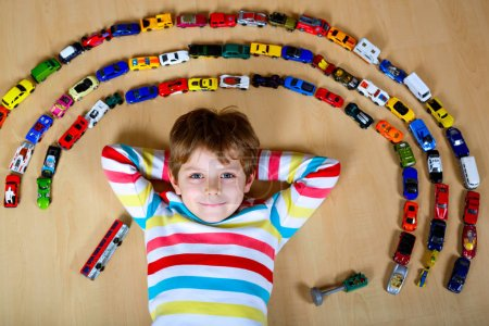 Photo for Cute little blond kid boy playing with lots of toy cars indoor. Child wearing colorful shirt. Happy preschooler having fun at home or nursery. Big collection of different vehicles. Happiness game - Royalty Free Image