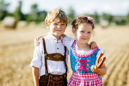 Two kids in traditional Bavarian costumes in wheat...