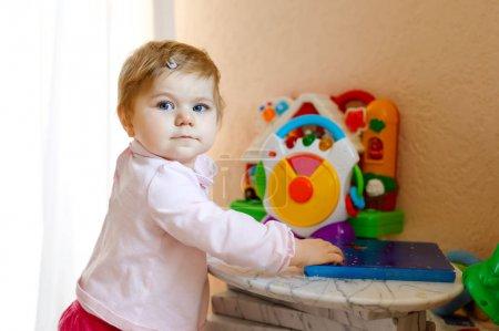 Photo pour Belle jolie jolie jolie petite fille jouant avec des jouets éducatifs à la maison ou à la crèche. Joyeux enfant en santé, amusez-vous avec des jouets colorés. Enfant apprenant différentes compétences - image libre de droit