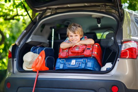 Photo for Adorable little kid boy sitting in car trunk just before leaving for summer vacation with his parents. Happy child with suitcases and toys going on journey. - Royalty Free Image