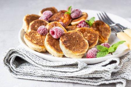 Photo pour Mini crêpes avec framboises, menthe et confiture pour le petit déjeuner sur une assiette en céramique. Crêpes cuites pour le petit déjeuner dans la cuisine. - image libre de droit