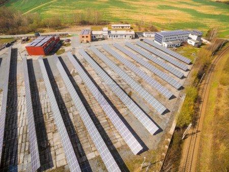 Photo pour Vue aérienne de la centrale solaire dans le paysage agricole. Arrière-plan industriel sur le thème des ressources renouvelables. - image libre de droit