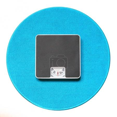 Photo pour Retro style weighing machine on a blue carpet. Sliming, dieting and healthy lifestyle theme. - image libre de droit