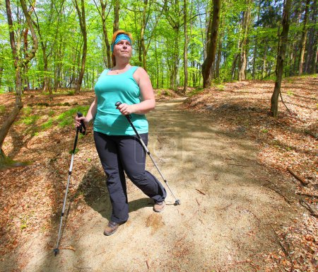 Overweight woman walking on meadow trail. Slimming and active lifestyle theme.