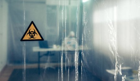 Photo for Protective curtain with biohazard symbol through which a scientist is seen working - Royalty Free Image