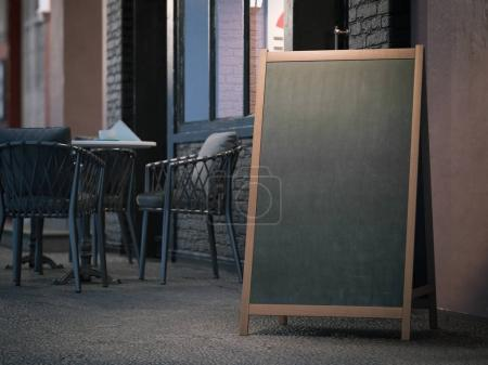Blank black menu board on sidewalk. 3d rendering