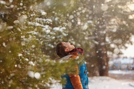 Cute little boy catching snowflakes with his tongue while walking in winter sunny day.