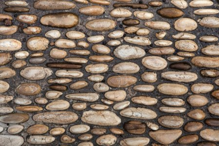 Photo for Cobbled pavement made of river rounded pebbles in Cordoba, Andalusia, Spain. Background texture. - Royalty Free Image