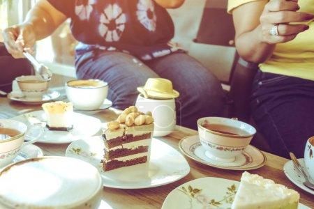 Photo pour Bonheur amies se rencontrent et boivent du thé ou du café avec des gâteaux ensemble au café dans l'après-midi. Les personnes, les loisirs et la communication. Approche sélective. - image libre de droit