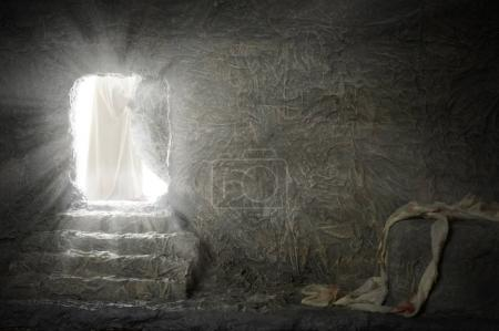 Jesus leaving empty tomb while light shines from t...