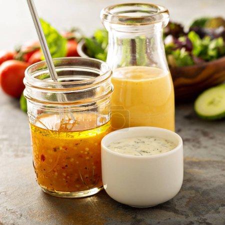 Photo pour Variété de sauces maison et sauces à salade dans des bocaux, y compris la vinaigrette, le ranch et la moutarde au miel - image libre de droit