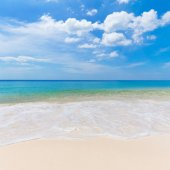 Sunny tropical beach with white sand and blue sky