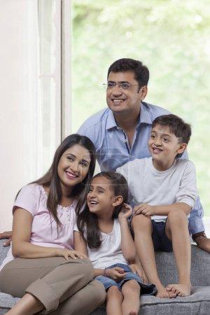familie mit zwei kindern sitzen sofa