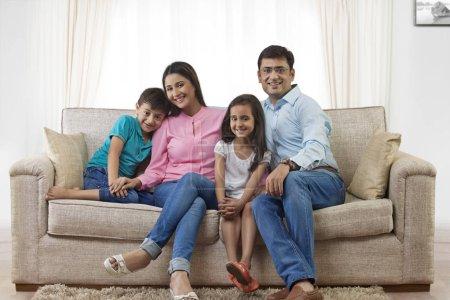familie mit zwei kindern auf sofa
