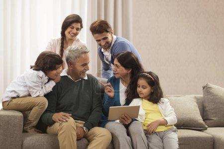 family looking at digital tablet