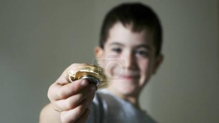Boy holding fidget spinner golden toy