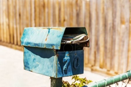 Rusty turquoise letter box on Australian summers d...