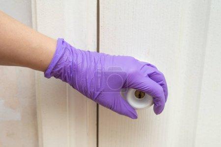 Foto de Mango de puerta en la guante de látex - Imagen libre de derechos