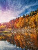 River in deep autumn mountain forest.
