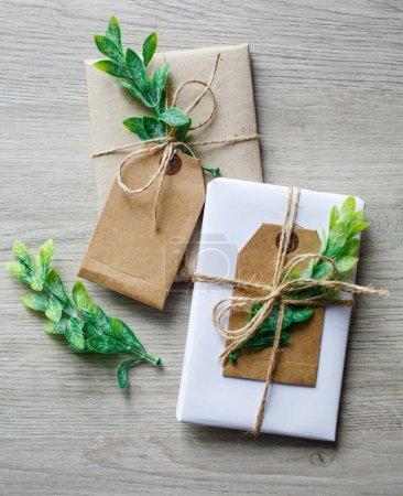 Photo pour Composition avec des boîtes à cadeaux artisanales de style naturel, des éléments de décoration florale et un arc en ficelle rustique sur fond en bois. Emballage cadeau éco-style en papier d'artisanat. Vue de dessus, à plat. - image libre de droit