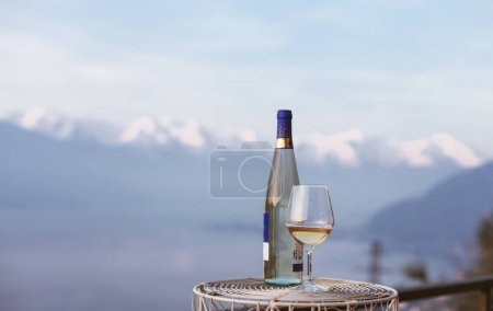 A glass of wine and a bottle of wine with a mountains view
